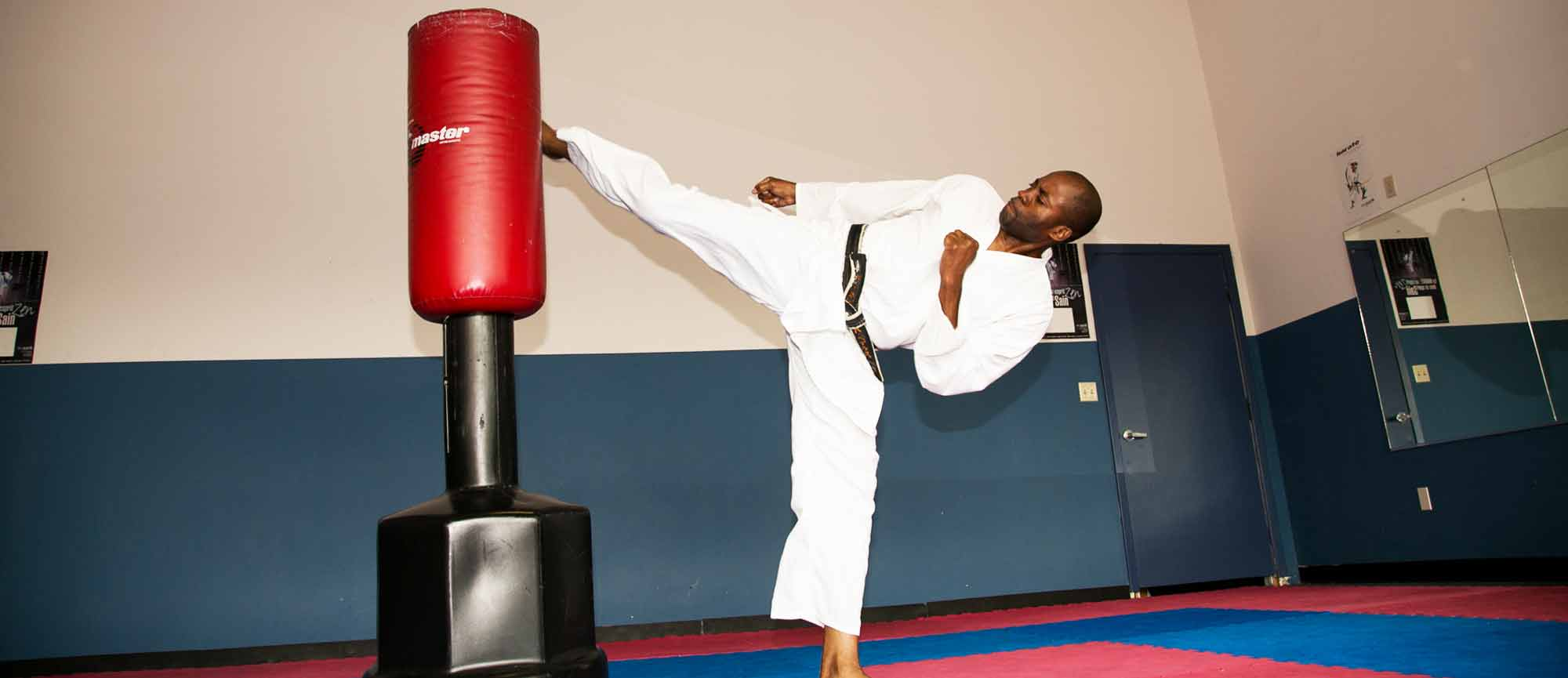 Alex Ndem kicking in Olympic Karate and Sports Center Houston dojo